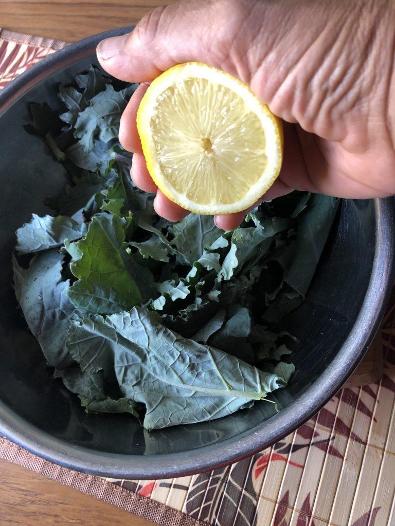 Squeezing lemon on kale